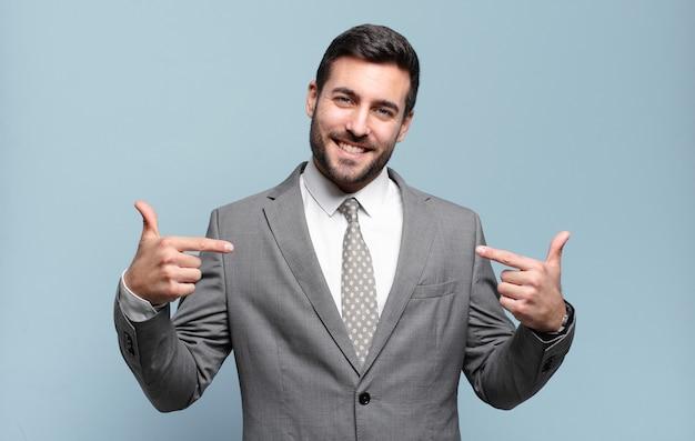 誇り高く、傲慢で、幸せで、驚き、満足しているように見え、自己を指し、勝者のように感じている若い大人のハンサムなビジネスマン
