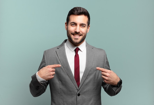 Young adult handsome businessman looking proud, positive and casual pointing to chest with both hands
