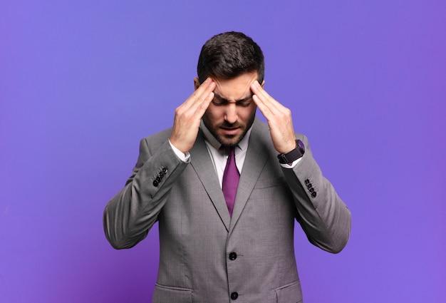 ストレスと欲求不満を見て、頭痛でプレッシャーの下で働いて、問題に悩まされている若い大人のハンサムなビジネスマン