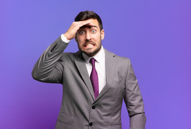 Молодой взрослый красивый бизнесмен в панике из-за забытого крайнего срока, чувствует стресс, вынужден скрывать беспорядок или ошибку