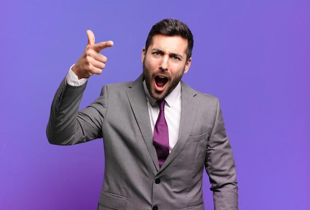猛烈な、狂った上司のように見える怒っている攻撃的な表情であなたを指している若い大人のハンサムなビジネスマン