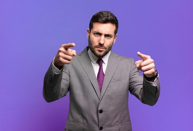 손가락과 화난 표정으로 카메라를 앞으로 가리키는 젊은 성인 잘 생긴 사업가, 당신의 의무를 다하라고