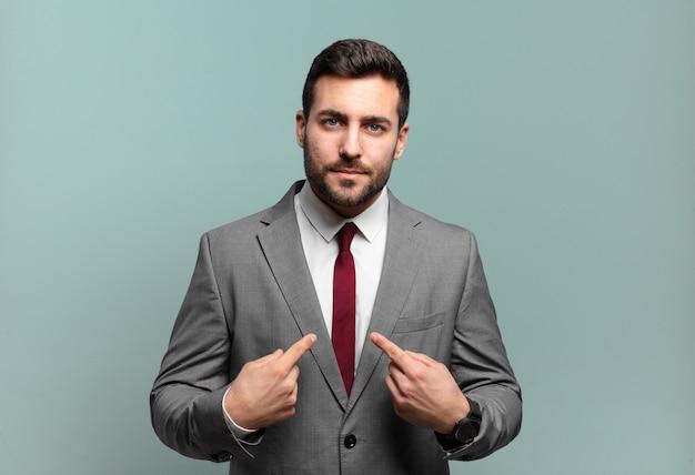 Молодой взрослый красивый бизнесмен, указывая на себя растерянным и насмешливым взглядом, шокирован и удивлен тем, что его выбрали