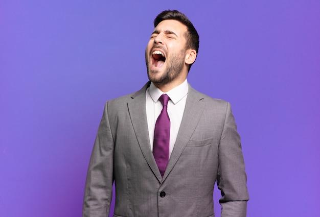 若い大人のハンサムなビジネスマンが猛烈に叫び、積極的に叫ぶ