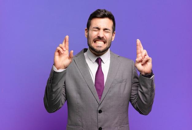 若い大人のハンサムなビジネスマンは笑顔で心配そうに両指を交差させ、心配を感じ、幸運を願ったり期待したりします