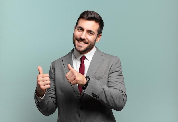 젊고 잘생긴 사업가는 옆에 있는 복사 공간을 가리키며 유쾌하고 부담 없이 웃고 행복하고 만족합니다.