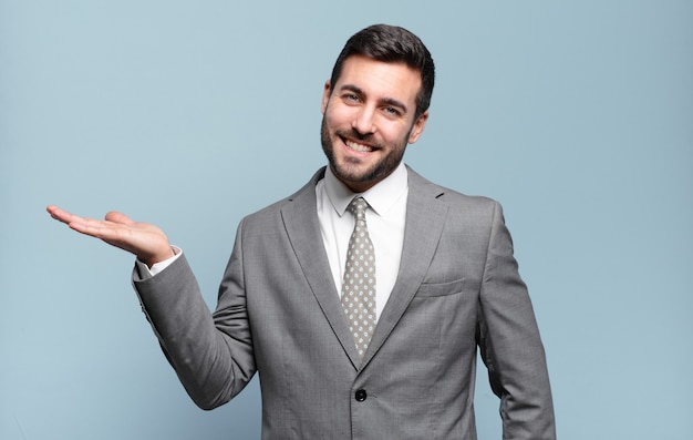 Young adult handsome businessman smiling, feeling confident, successful and happy, showing concept or idea on copy space on the side