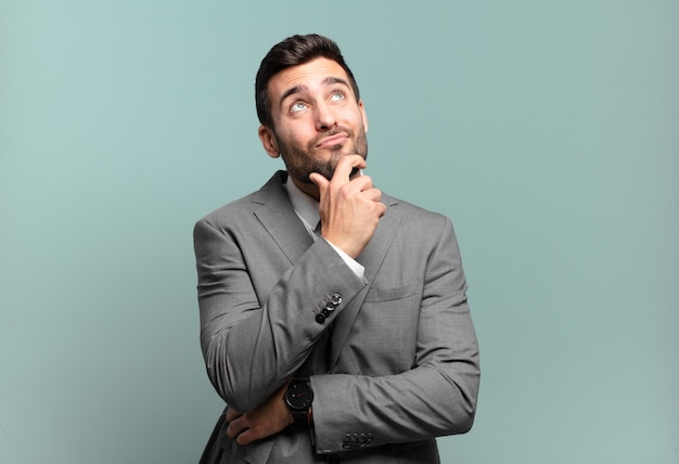 Young adult handsome businessman thinking, feeling doubtful and confused, with different options, wondering which decision to make