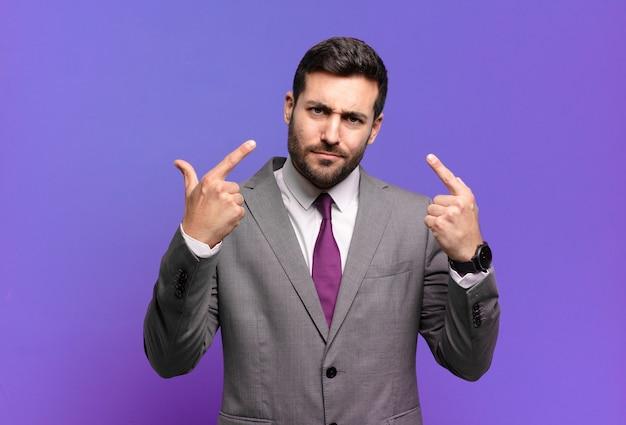 Молодой взрослый красивый бизнесмен с плохим отношением, выглядит гордым и агрессивным, указывая вверх или весело жестикулируя руками