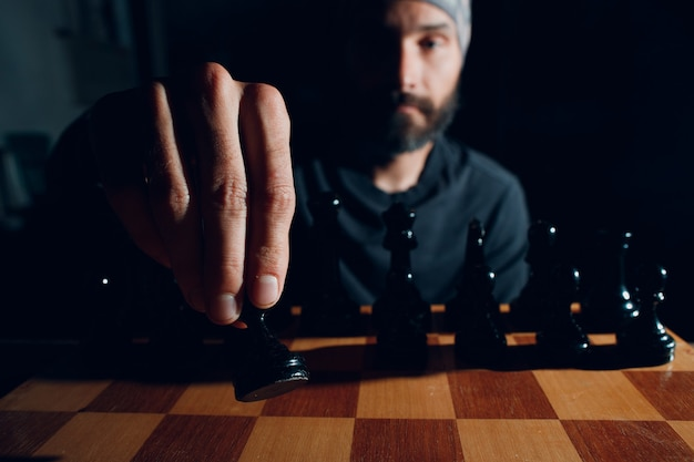 Young adult handsome man playing chess board in dark with side lit.
