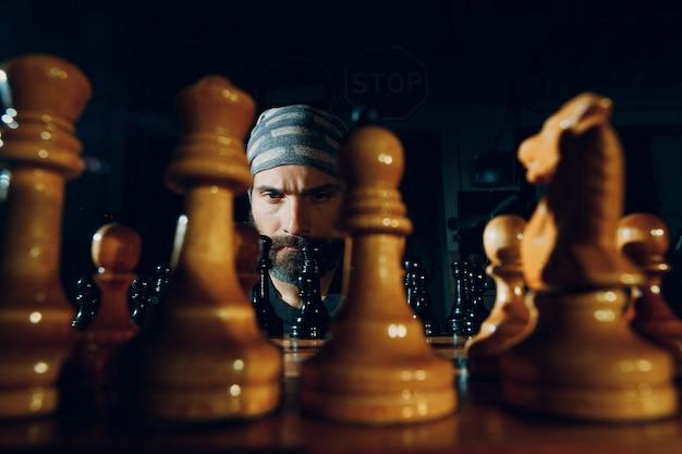 Молодой взрослый красивый мужчина играет на шахматной доске в темноте с боковой подсветкой.