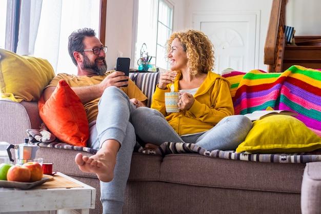 若い大人の幸せなカップルは朝食時に屋内で余暇活動を楽しんでいます-男性は電話を使用し、女性はコーヒーやお茶を飲みます-ソファに座って家を楽しんでいる人々の笑顔と幸せ