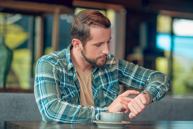 夢のように横を探している夏のカフェでコーヒーを飲みながら若い大人の幸せな男