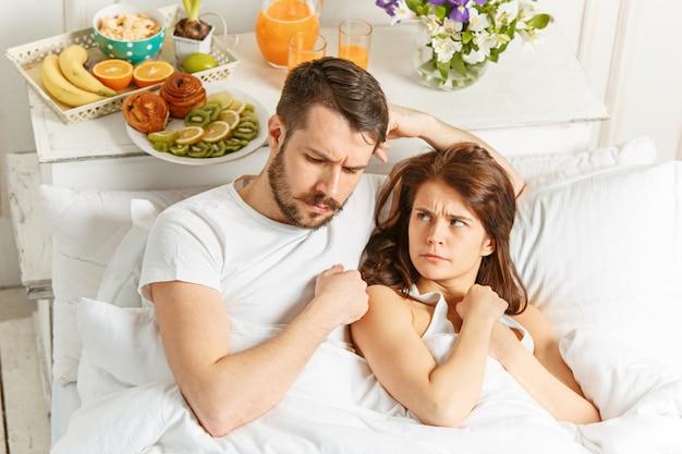 Giovane coppia eterosessuale adulta sdraiato sul letto in camera da letto