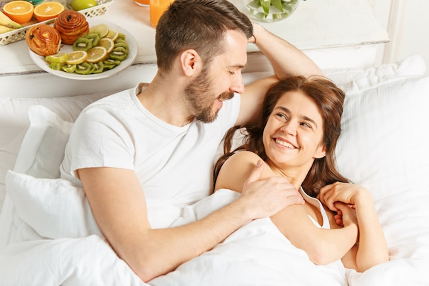 Young adult heterosexual couple lying on bed in bedroom