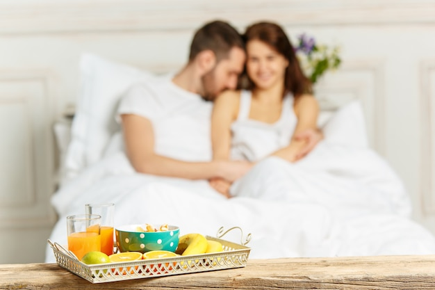 Young adult heterosexual couple lying on bed in bedroom Free Photo