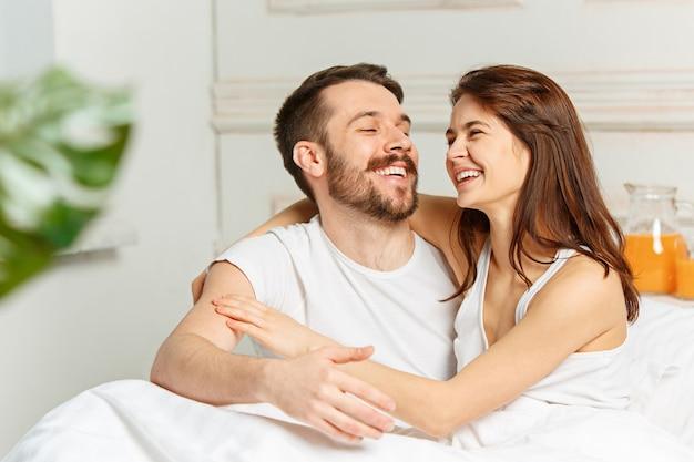 Young adult heterosexual couple lying on bed in bedroom