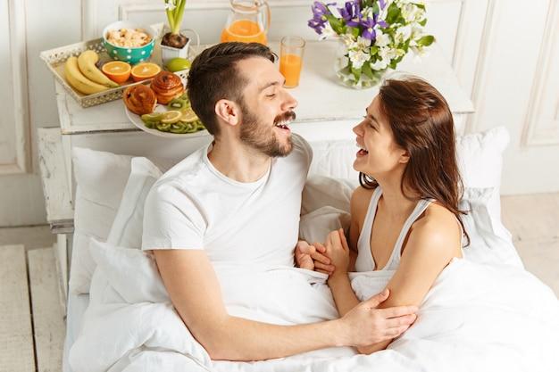 침실에서 침대에 누워 젊은 성인 이성애 커플