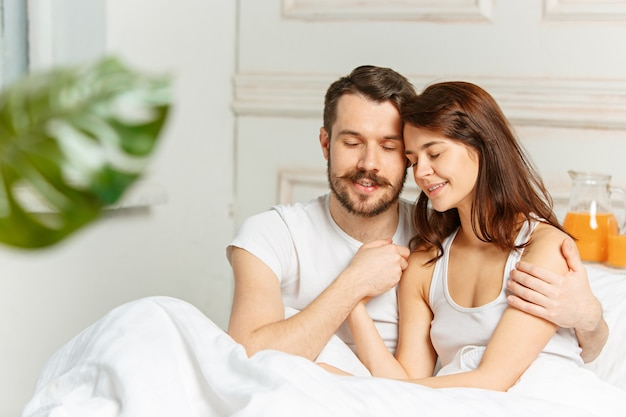 寝室のベッドに横たわっている若い大人の異性愛者のカップル