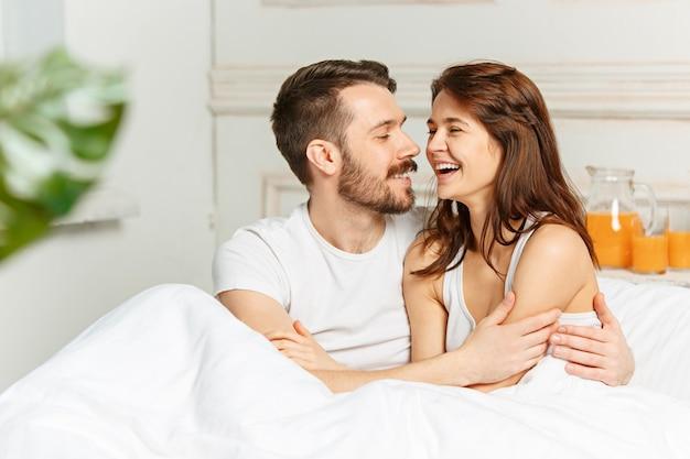 Молодые взрослые гетеросексуальные пары, лежа на кровати в спальне