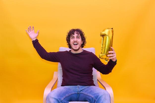 Молодой взрослый держит воздушный шар номер один. празднование победы в видеоиграх. на изолированном желтом фоне.