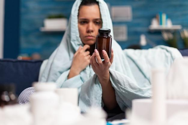 病気の薬の瓶容器を保持している若い大人