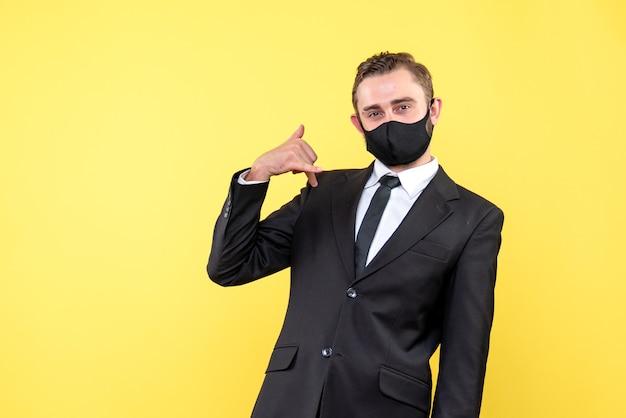 私に連絡ジェスチャーをする医療フェイシャルマスクの若い大人