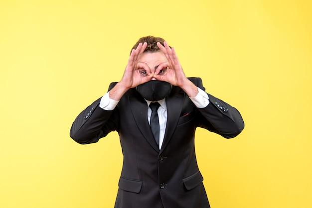 Молодой человек в медицинской маске, делая жест очки