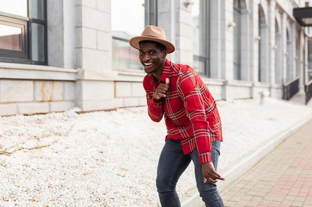 Молодой человек в красной рубашке танцует
