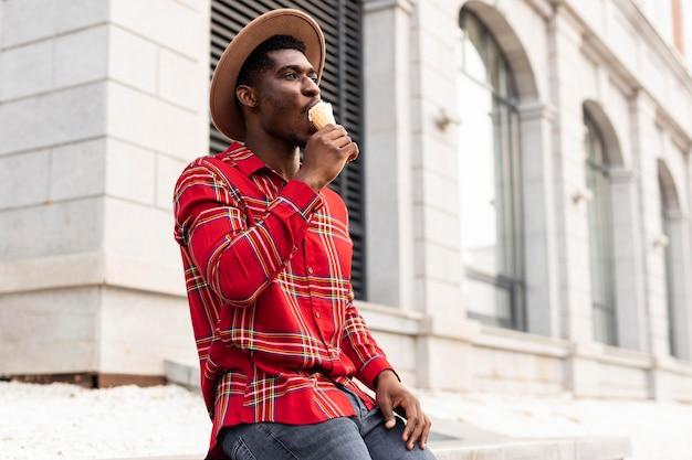 アイスクリームの低いビューを楽しんでいる赤いシャツの若い大人
