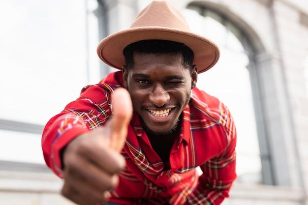 Молодой человек в красной рубашке показывает палец вверх жест
