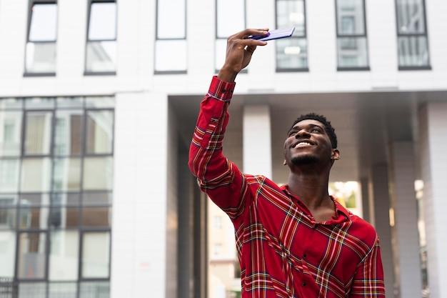 Молодой человек в красной рубашке, путешествующий по городу