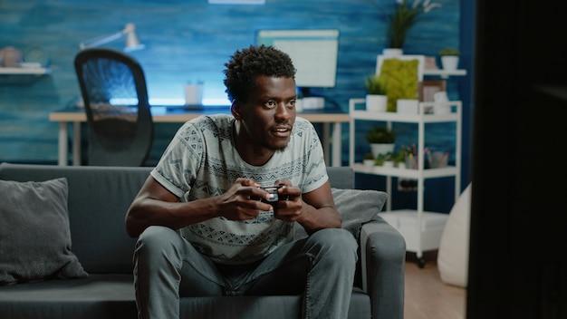 ジョイスティックでテレビコンソールのビデオゲームで負ける若い大人