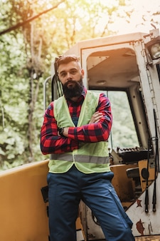 Young adult lumberjack or logger standing in front of huge bagger excavator in the woods