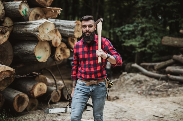 Young adult lumberjack or logger standing and posing in the woods. he holding big axe and chainsaw.