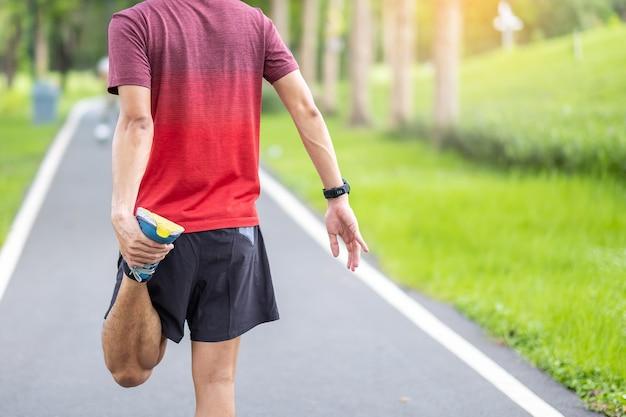 Молодой взрослый мужчина в красной спортивной одежде, растягивая мышцы в парке на открытом воздухе