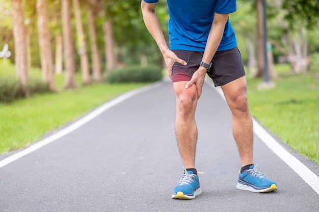 Young adult male with muscle pain during running. runner have leg ache due to iliotibial band syndrome – itbs. sports injuries and medical concept