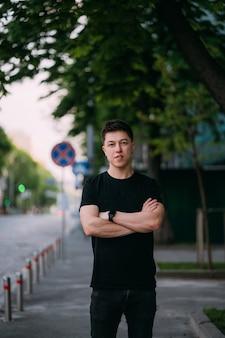 Il giovane uomo adulto in una maglietta nera e jeans cammina su una strada cittadina