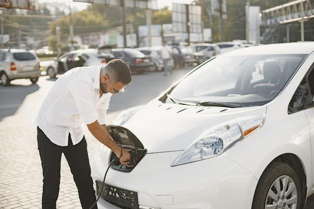 Giovane uomo adulto che carica la sua auto elettrica in città. concetto di auto elettrica ecologica.