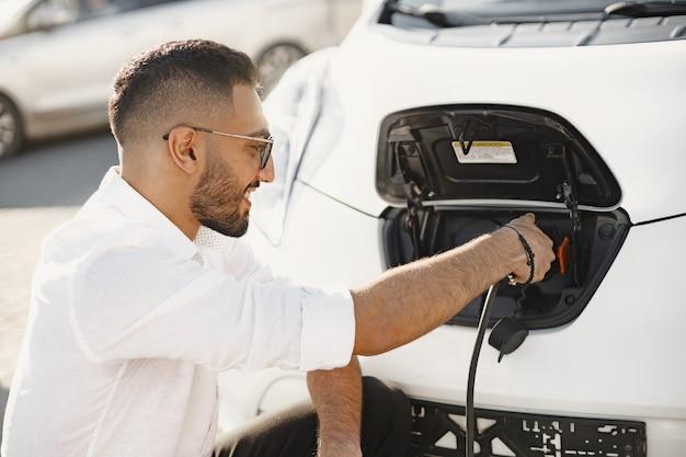 Молодой взрослый человек заряжает свой электромобиль в городе. эко-концепция электромобиля.
