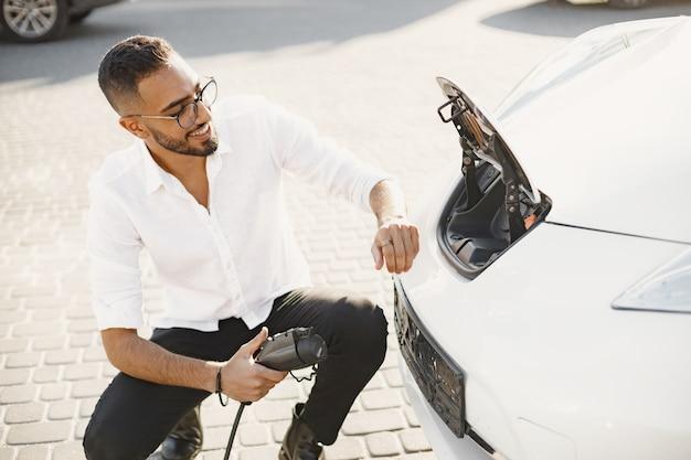 市内で電気自動車を充電している若い成人男性。エコ電気自動車のコンセプト。