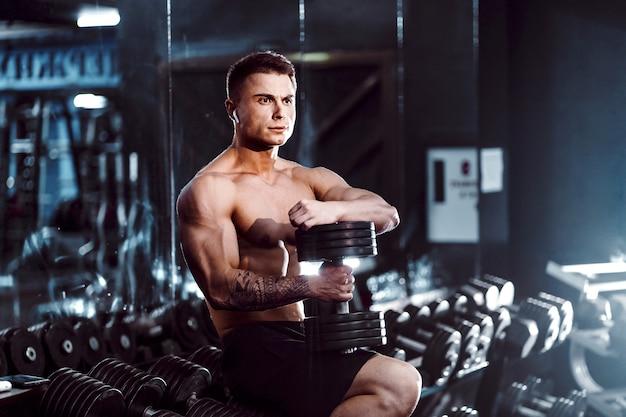 若い成人男性ハンサムなアスリートジムでワークアウト、ベンチに座って、上げられた腕でダンベルを保持しています。屋内、見かけの重量