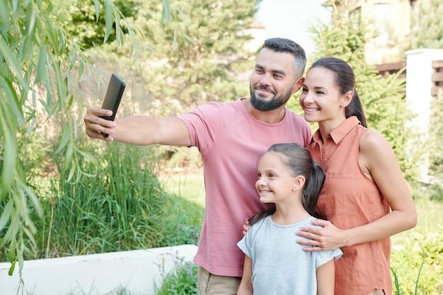 晴れた夏の日に裏庭で彼と彼の妻と娘の自撮り写真を撮るスマートフォンを持っている若い成人男性