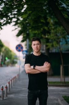 黒のtシャツとジーンズの若い大人の男が街の通りを歩く