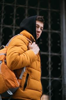 Молодой взрослый человек в желтой куртке ходит на фоне кованые решетки.