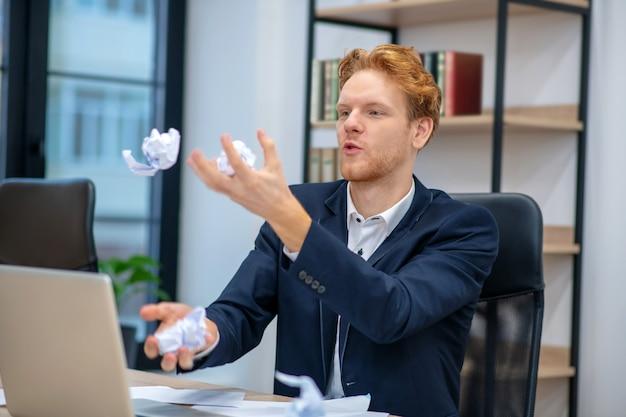 Молодой взрослый мужчина в деловом костюме жонглировал мятой бумагой, сидя на рабочем месте в офисе