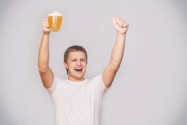 스튜디오의 외진 배경에 흰색 티셔츠를 입고 맥주 한 잔을 들고 유럽풍의 젊은 성인 남성