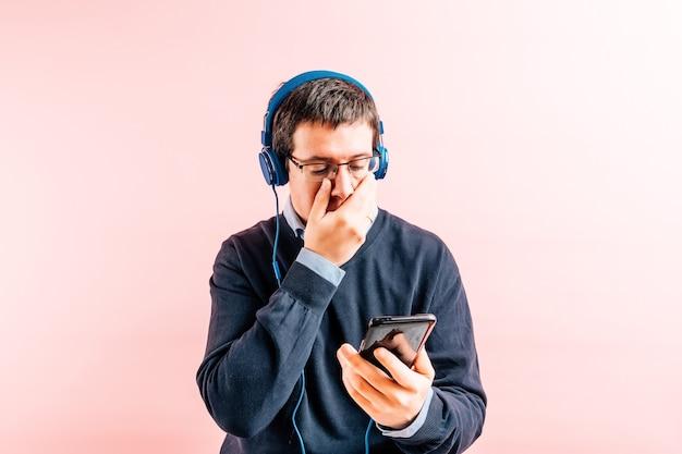 안경, 헤드폰, 스마트폰이 달린 분홍색 배경의 셔츠와 파란색 v넥 스웨터를 입은 35세의 젊은 성인 남성은 걱정스러운 얼굴을 가리고 있습니다.