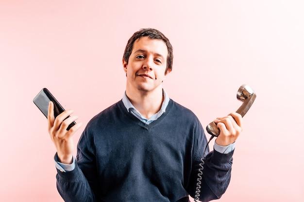 Молодой взрослый мужчина тридцати пяти лет в рубашке и синем свитере с v-образным вырезом на розовом фоне с озорной улыбкой держит смартфон и традиционный проводной телефон. концепция технологии