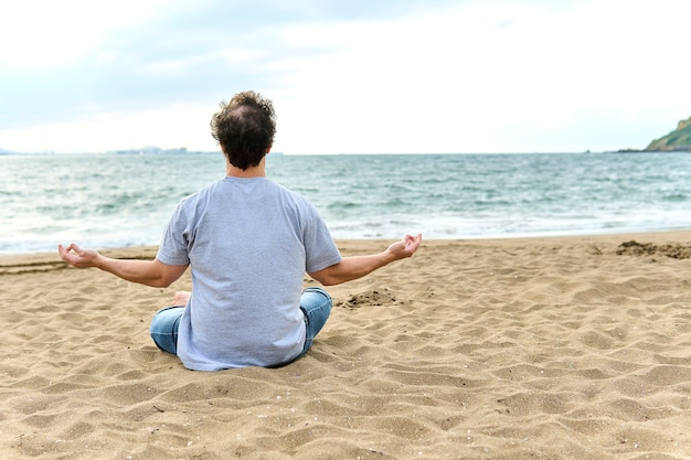 瞑想するヨガの位置に座ってビーチで若い大人の男